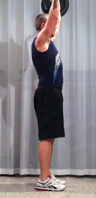 Bodypump-teknik, frivändning: stången är högt över huvudet, blicken riktad rakt fram, armbågarna är lätt böjda