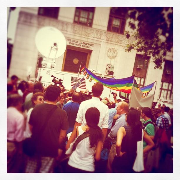 Folksamling med regnbågsflaggor och journalistbussar med stora paraboler